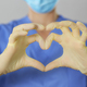 Hands in rubber gloves making the heart symbol in front of a healthcare professional in uniform - PhotoDune Item for Sale