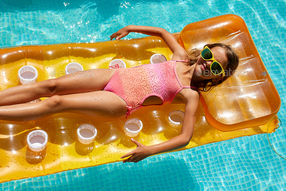 Little girl in sunglasses relaxing in swimming pool, swims on inflatable yellow mattres - Stock Photo - Images
