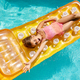 Happy little girl has fun in swimming pool, swims on inflatable yellow mattress - PhotoDune Item for Sale