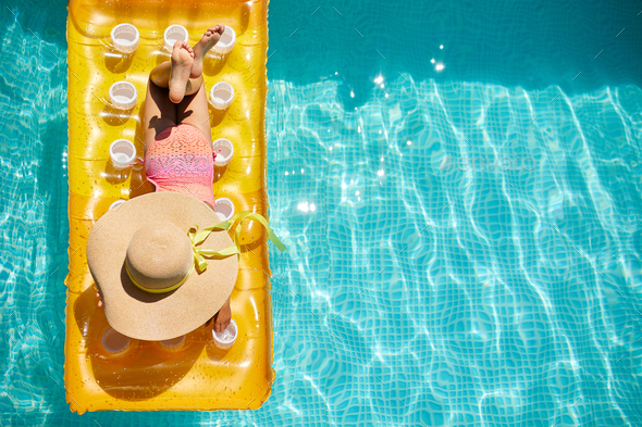 Top view little girl in hat relaxing in swimming pool, swims on inflatable yellow mattress - Stock Photo - Images