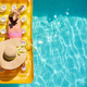 Top view little girl in hat relaxing in swimming pool, swims on inflatable yellow mattress - PhotoDune Item for Sale