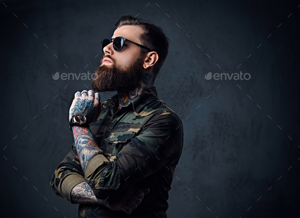 Portrait of bearded tattooed hipster male dressed in a military jacket. - Stock Photo - Images