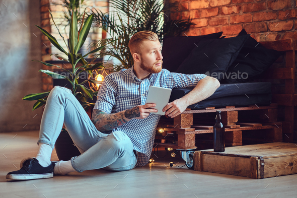 The full body image of blond stylish male using a tablet PC. - Stock Photo - Images
