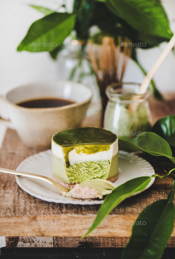 Green matcha cheesecake and coffee in mug on kitchen counter - Stock Photo - Images