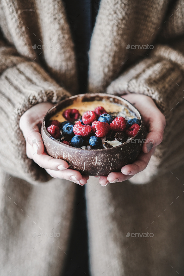 Healthy vegan breakfast bowl with oats in womans hands - Stock Photo - Images