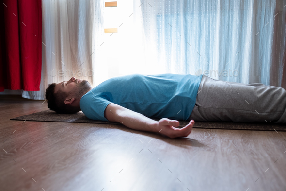 Young man meditating on a floor and lying in Shavasana pose at his living room. - Stock Photo - Images