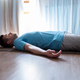 Young man meditating on a floor and lying in Shavasana pose at his living room. - PhotoDune Item for Sale