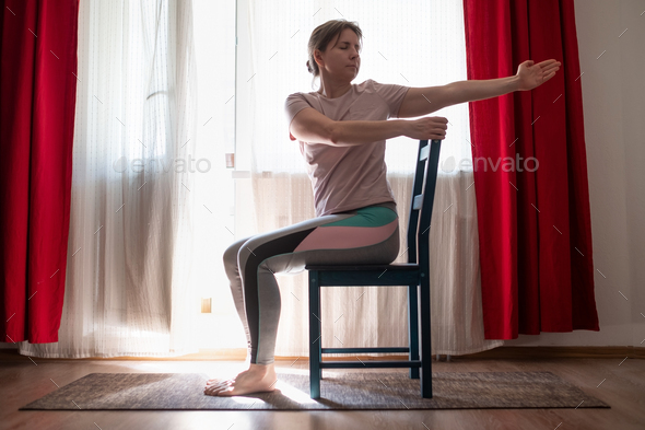 Woman working out doing yoga or pilates exercise using chair. - Stock Photo - Images