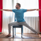 Caucasian young man in Warrior 2 Pose using chair at his living room - PhotoDune Item for Sale