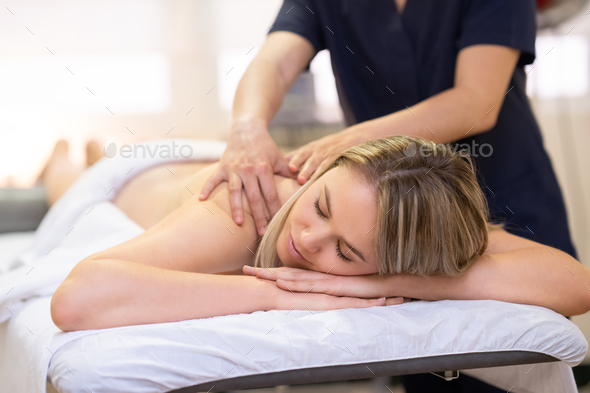 Woman lying on a stretcher receiving a back massage - Stock Photo - Images