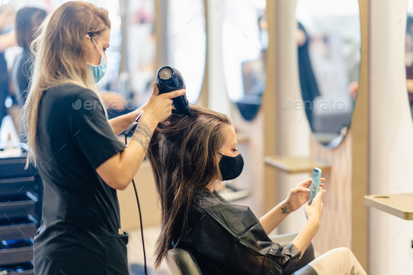 Hairdresser drying her client's hair with a hairdryer wearing protective masks in a beauty - Stock Photo - Images