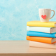 Stack of books and mug on wooden table - PhotoDune Item for Sale