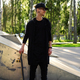 A man in black clothes posing with skateboard. - PhotoDune Item for Sale