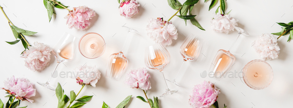 Rose wine in glasses and blossom peonies over white background - Stock Photo - Images