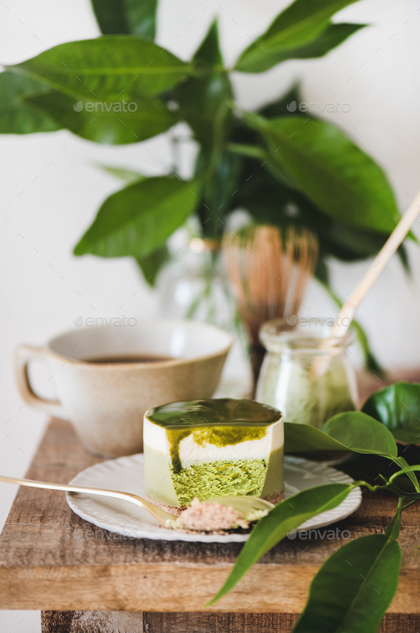 Green matcha cheesecake and black coffee on kitchen counter - Stock Photo - Images