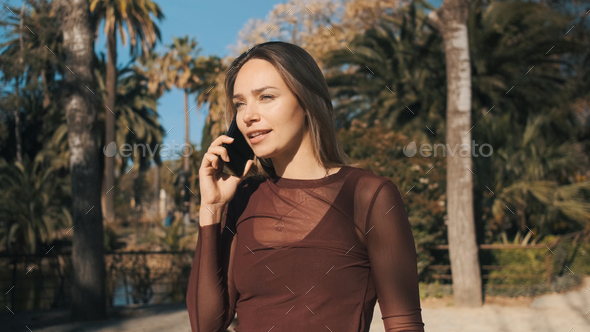 Beautiful girl intently talking on phone with boyfriend during walk along city park