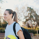 Beautiful girl with backpack and football walking through city park after morning training outdoor - PhotoDune Item for Sale