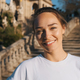 Beautiful smiling girl in t-shirt happily looking in camera resting in park with old architecture - PhotoDune Item for Sale