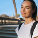 Portrait of attractive smiling girl with backpack confidently looking in camera outdoor - PhotoDune Item for Sale
