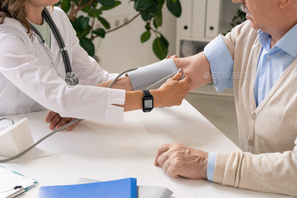 Young clinician in whitecoat putting on part of tonometer on arm of senior man - Stock Photo - Images