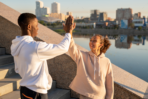Happy young female and African sportsman in hoodies giving each other high five - Stock Photo - Images