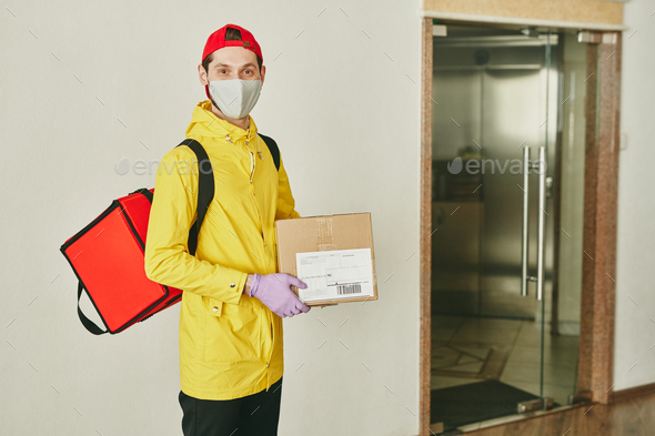 Happy young courier with big red backpack and cardboard packed box in hands - Stock Photo - Images