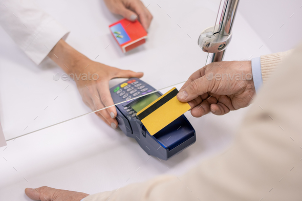 Hand of modern senior man paying by plastic card for medicine in drugstore - Stock Photo - Images