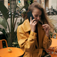 Beautiful stylish girl in color leather coat talking on phone in cozy cafe on street - PhotoDune Item for Sale
