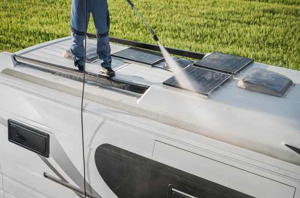 RV Industry Worker Cleaning Camper Van Roof and Motorhome Solar Panels - Stock Photo - Images