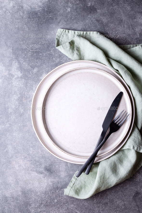 Plates, Black Cutlery and Linen Napkin on Stone Table. - Stock Photo - Images