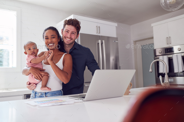 Portrait Of Family With Baby Daughter In Kitchen Using Laptop On Counter - Stock Photo - Images