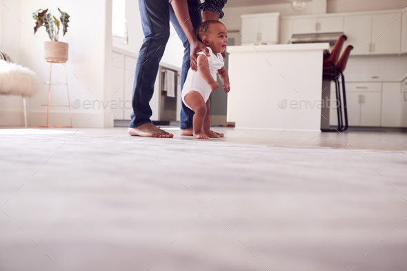 Father Encouraging Smiling Baby Daughter To Take First Steps And Walk At Home - Stock Photo - Images