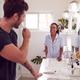 Couple Wearing Pyjamas Standing In Bathroom At Sink Brushing Teeth In The Morning - PhotoDune Item for Sale