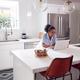 Woman Wearing Pyjamas In Kitchen Making Online Credit Card On Laptop - PhotoDune Item for Sale