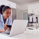 Woman Wearing Pyjamas In Kitchen Making Online Credit Card On Laptop - PhotoDune Item for Sale