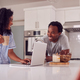 Couple Wearing Pyjamas Standing In Kitchen Working From Home On Laptop - PhotoDune Item for Sale