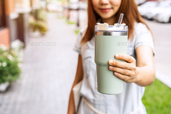 Young asian woman holding a reusable tumbler glass and walking in the city, Zero waste concept - Stock Photo - Images
