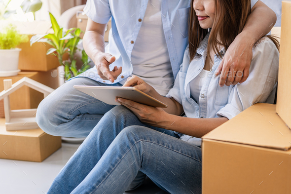 Young happy couple moving in new house and looking for home decorating ideas - Stock Photo - Images