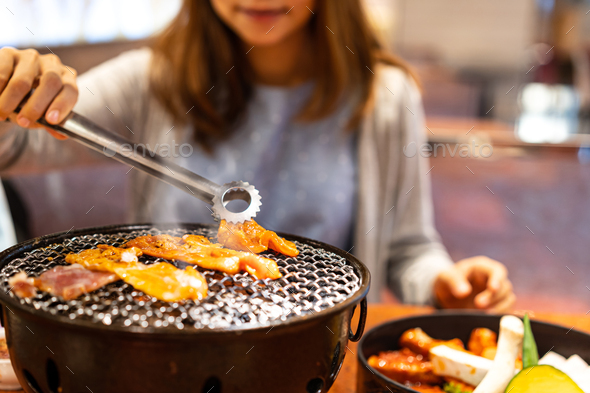 Young asian eating korean barbecue yakiniku in restaurant - Stock Photo - Images