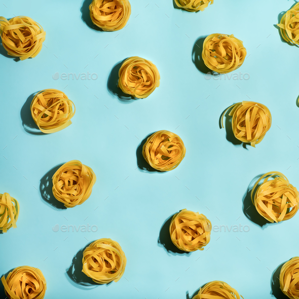 Pasta art with tagliatelle on blue background - Stock Photo - Images
