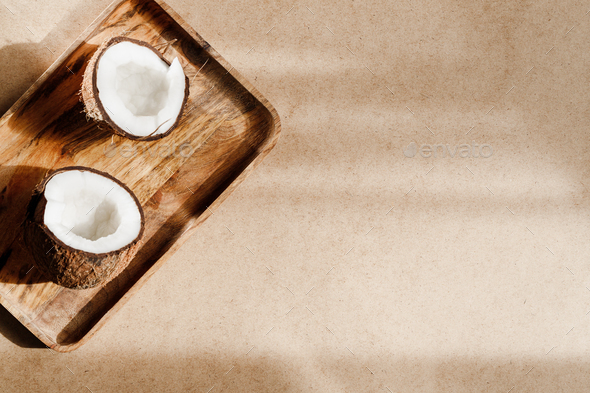 Summer abstract creative composition with coconut a on wooden tray over kraft paper. - Stock Photo - Images