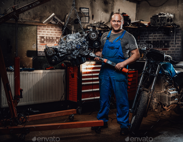Professional mechanic stands next to the suspended flat engine and naked bike in garage - Stock Photo - Images