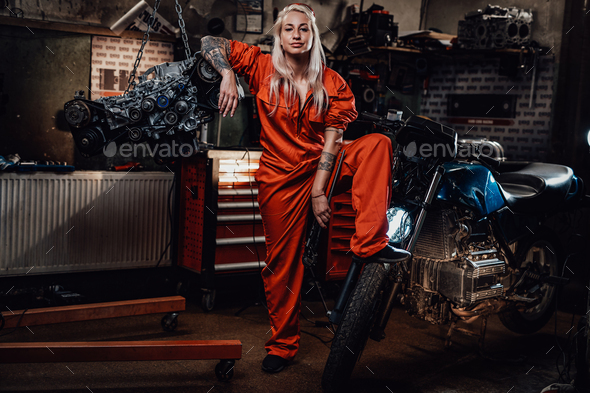 Blond female mechanic with tattooed hands in orange overalls stands in garage or workshop - Stock Photo - Images