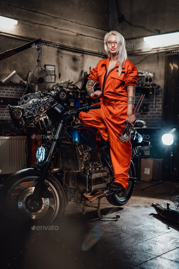 Beautiful female mechanic in orange overalls hold a big wrench and posing for a camera in garage - Stock Photo - Images