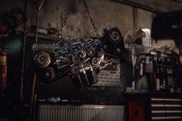 Suspended boxer engine in a dark garage or workshop - Stock Photo - Images