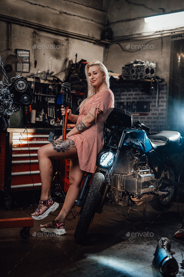 Beautiful blonde girl with tattooed body wearing pink dress posing in garage or workshop - Stock Photo - Images