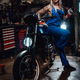Female tattooed mechanic in work overalls hold a big wrench and posing for a camera in garage - PhotoDune Item for Sale