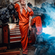 Blond female mechanic with tattooed hands in orange overalls stands in garage or workshop - PhotoDune Item for Sale