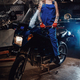 Blond female mechanic with tattooed hands wearing work overalls posing on her sportbike in garage - PhotoDune Item for Sale