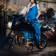 Female mechanic relaxing smoking a cigarette while standing on sportbike in garage or workshop - PhotoDune Item for Sale